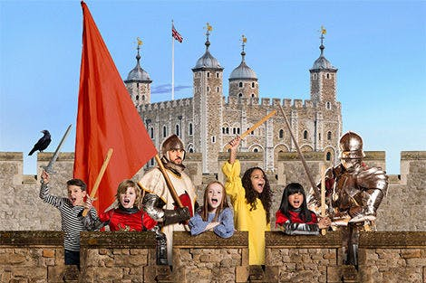 A group of children and two knights standing in front of the White Tower.