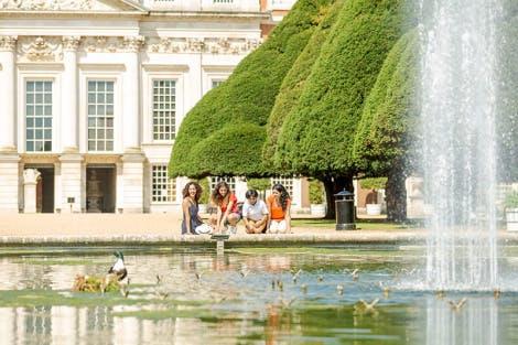 Family enjoy Hampton Court Palace on a sunny day