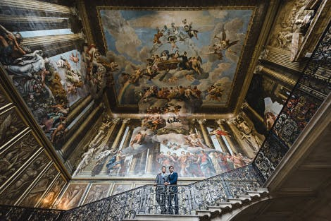 Two grooms stand on the dramatic baroque painted staircase of Hampton Court Palace looking down at the camera
