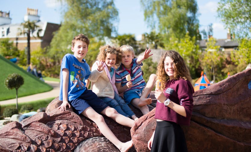 Four children on top of the dragon sculpture in the Magic Garden