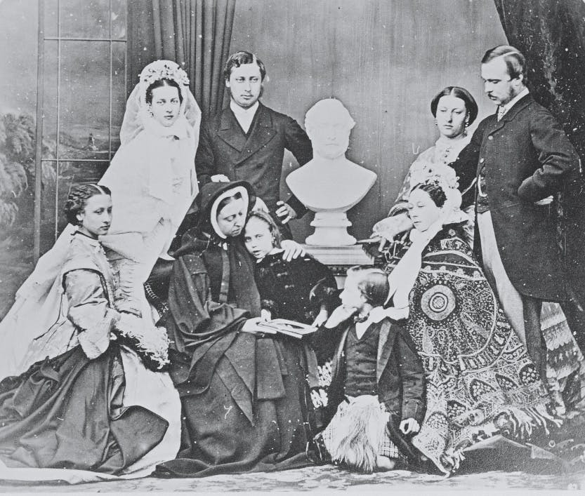 Group photograph, taken at Windsor, after the wedding of the Prince of Wales, April 1863, gathered around a bust of the Prince Consort. From left to right, standing: Alexandra, Princess of Wales; the Prince of Wales; Princess Helena; Prince Louis of Hesse. Seated: Princess Louise; Queen Victoria; Princess Beatrice; Prince Leopold; and Alice, Princess Louis of Hesse in ornate cloak and bonnet.