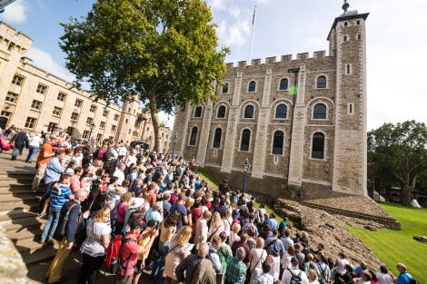 A large group congregates around a Yeoman Warder on the stairs outside the White Tower on a sunny day. Waterloo block can be seen to the left and the White Tower lawn to the right