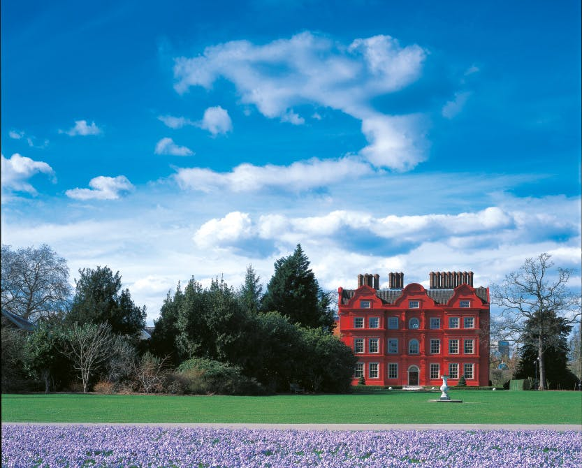 The South Front, Kew Palace's bright red brick front with blue skies above and Kew Gardens surrounding.