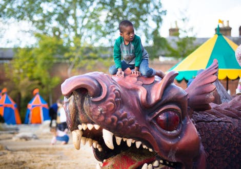 Boy playing on the large dragon sculpture in the Magic Garden
