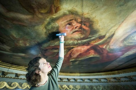 A conservator inspects a panel of the Rubens ceiling depicting James I at the Banqueting House, Whitehall