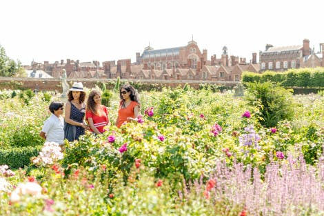 A family of two women, a boy and a girl relax and admire the colourful planting in the Rose Garden at Hampton Court Palace. The Tudor palace can be seen in the background