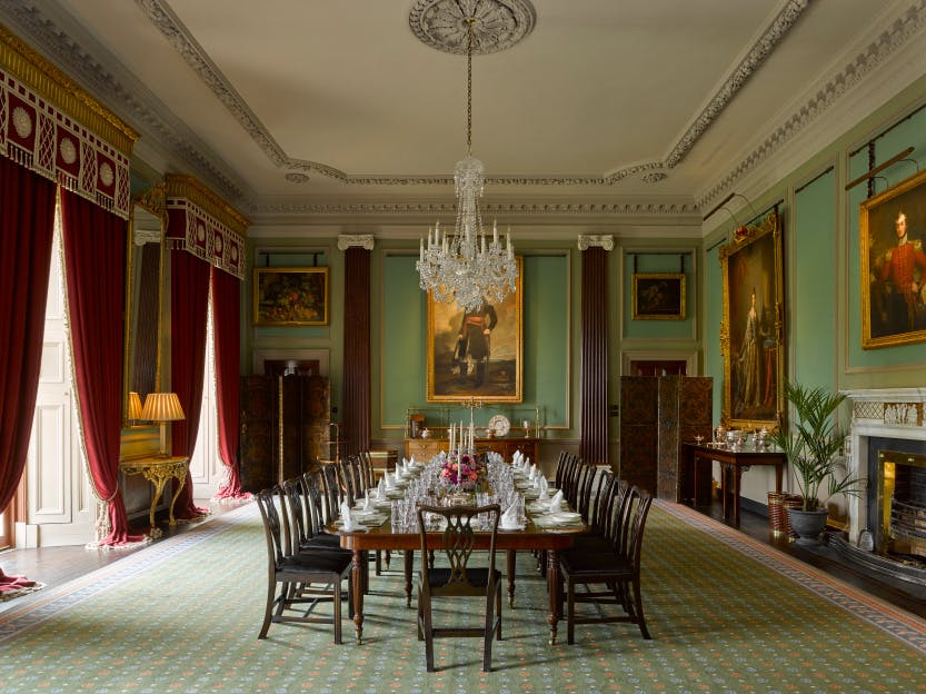 The State Dining Room, Hillsborough Castle, painted in a light green colour with a long mahogany dining table and red drapes across the windows.