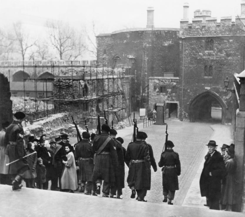 Visitors return to the Tower of London after the end of the Second World War. The Tower is visibly scarred by the effects of war and armed soldiers patrol the site
