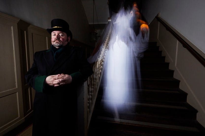 Hampton Court Warden standing on a staircase while a ghost appears behind him
