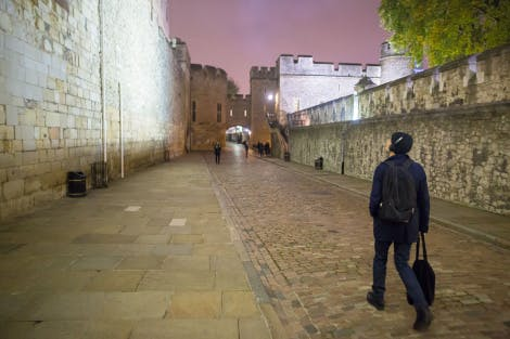 Male participant from the Nightwatchers experience walking through the Tower of London at night