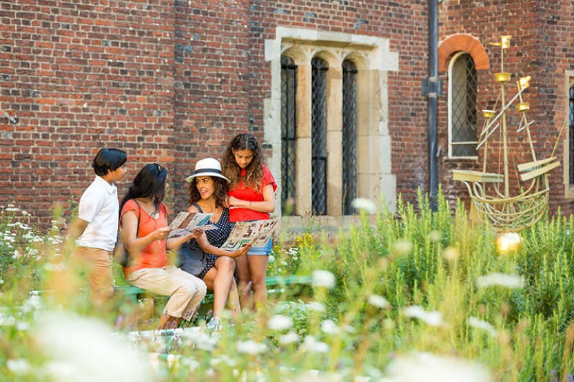 A family of two women, a boy and a girl smile and talk in Chapel Court at Hampton Court Palace. Planting can be seen in the foreground