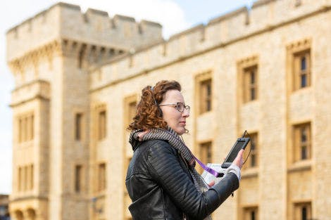 A visitor uses the audio guide outside the Jewel House at the Tower of London.