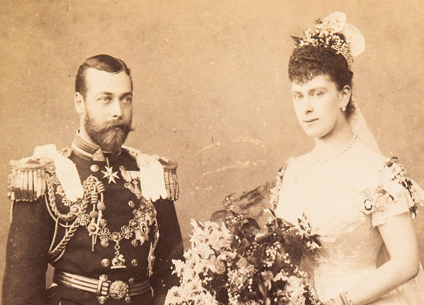 Old photograph of Prince George and Princess Mary of Teck in wedding outfits. The Duke wears naval uniform with the collar of the Order of the Garter and Mary of Teck wears a white satin wedding dress.