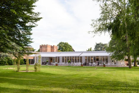 A large marquee stands on a lawn in the grounds of Hampton Court Palace, Surrey