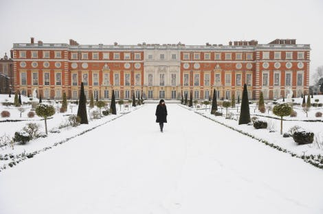 The South Front and the Privy Garden in snow, looking north. Showing a figure walking along the snowy avenue in the Privy Garden.