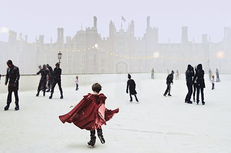 People skating on the ice rink outside the front of Hampton Court Palace