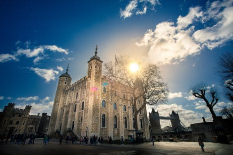 The White Tower exterior at the Tower of London under a blue, partially cloudy sky. Visitors can be seen exploring the grounds beneath the tower