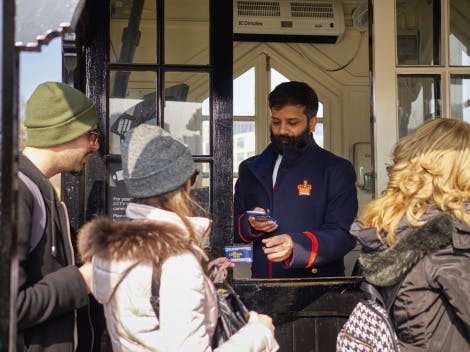 A male admissions staff member in uniform is shown checking the tickets of visitors at the main entrance to the Tower of London.