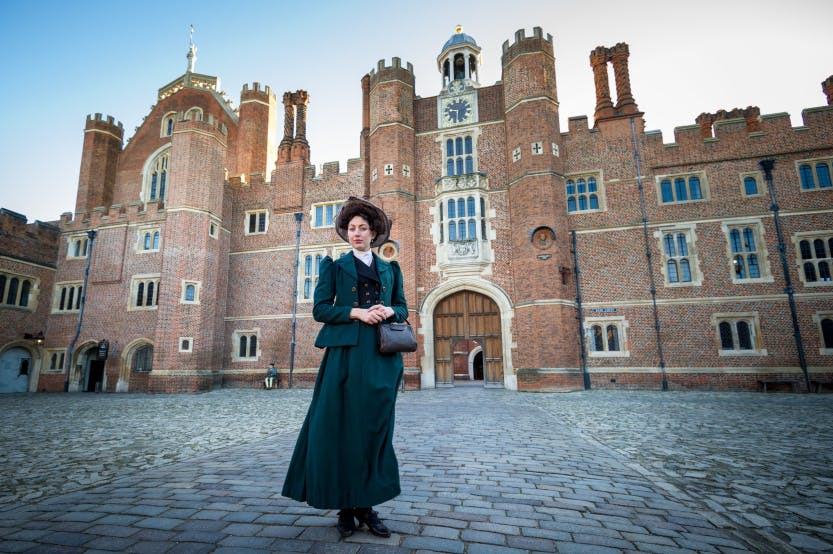 A suffragette stands outside Hampton Court Palace