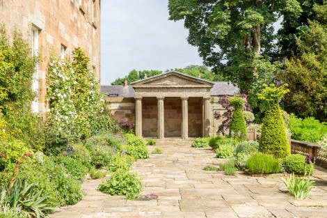 The South Terrace of Hillsborough Castle and Gardens, looking east towards the Greek Temple. Terrace flagstones and the Georgian exterior of the castle can be seen in the foreground under a partially cloudy sky and surrounded by bright green trees and other planting