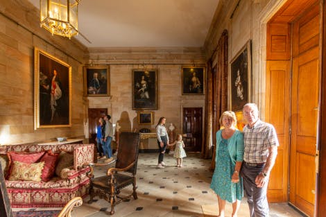 A middle-aged couple walk through the State Entrance Hall whilst other visitors explore behind them. The room features a stone-tiled floor with painted-effect stone walls. Large oil paintings and portraits in gold frames hang on the surrounding walls.