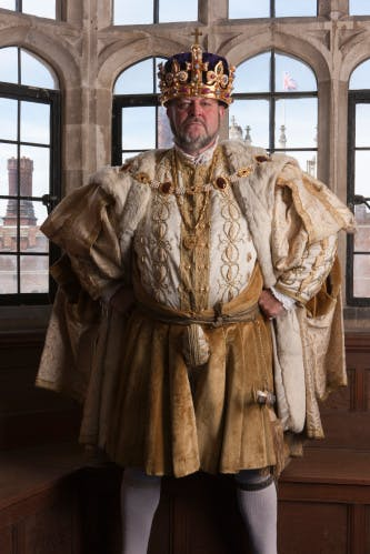 Live interpreter in the role of King Henry VIII, stood in front of a window and wearing Henry VIII's re-created Crown of State