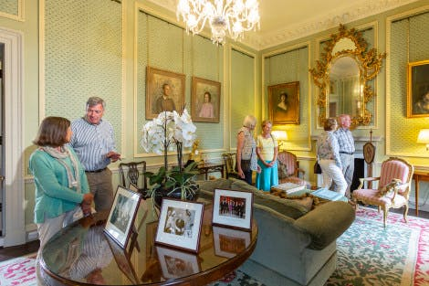 A group of visitors wander around Lady Grey's Study. A crystal chandelier hangs above the room which features a soft teal wallpaper, hand-block printed with a flower design