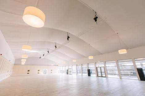 A large bright white events venue with French windows on the far side