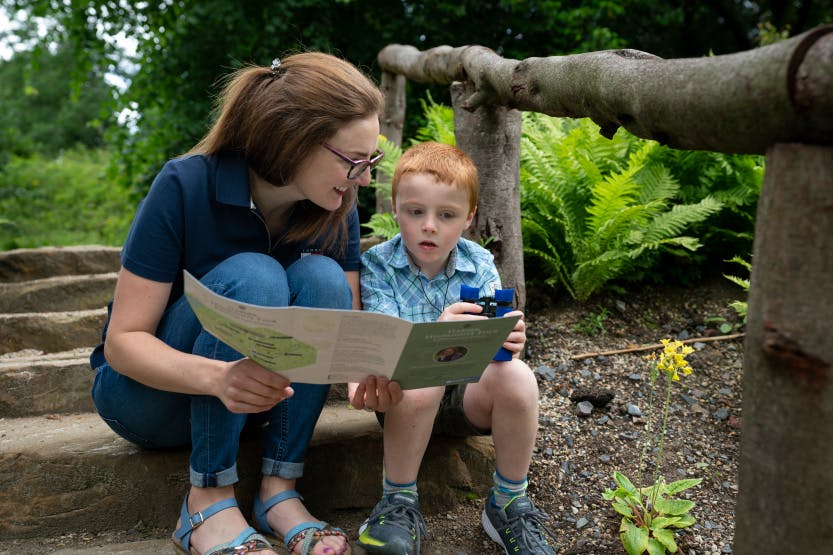 Mother and son sitting on concrete steps in the gardens looking at a garden paper trail.
