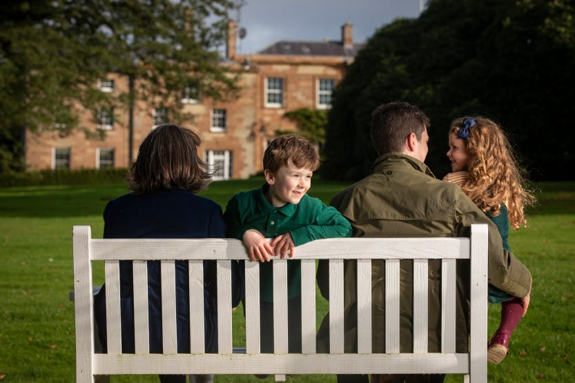 A family of two adults and two children enjoy playing and walking on the South Lawn of Hillsborough Castle and Gardens in autumn 2019.