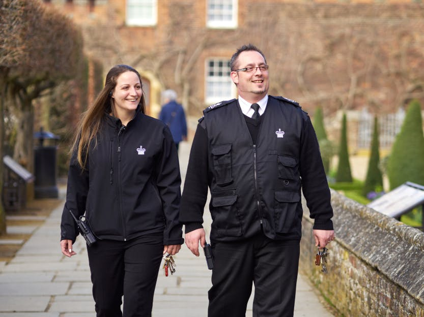 Male and female custody staff in black uniform walk side-by-side along path.