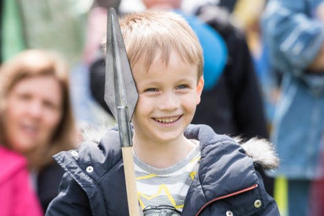 Young boy holding Tudor spear at a family event