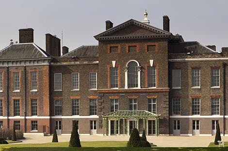 Bright sunny photo of the front of the brick built Kensington Palace and gardens.