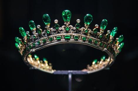 A diamond and emerald tiara mounted on a frame on a plain background
