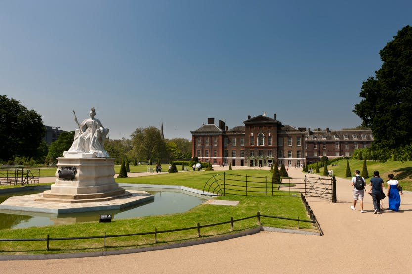 The East Front after Kensington Palace renovations looking south-west, 28 May 2012. Showing visitors to the palace. The statue of Queen Victoria (installed in 1893) is in the foreground.   The Kensington Palace project was an undertaking over two years (2010-12) of major refurbishments (renovation) at Kensington, including new gardens.