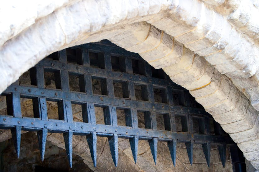 Iron spikes descending from a stone arch, a portcullis