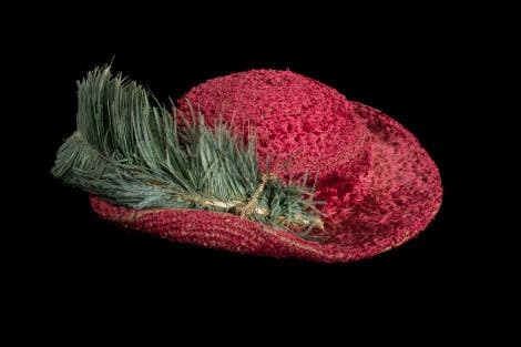 Tudor or early Stuart red hat with ostrich feather on black background