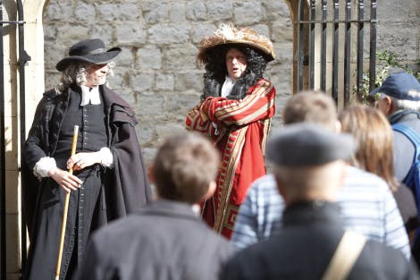 Two men dressed in historical costume performing to a crowd at the Tower of London. One man, wearing a red coat and a hat with a feather plume, is about to strike.