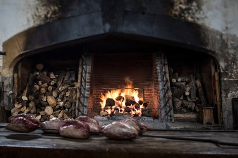The Great Kitchens, looking south towards the great roasting fire where logs are burning. Logs ready for burning are piled in alcoves on the left and right of the fire. In the foreground are models of joints of meat on a table.