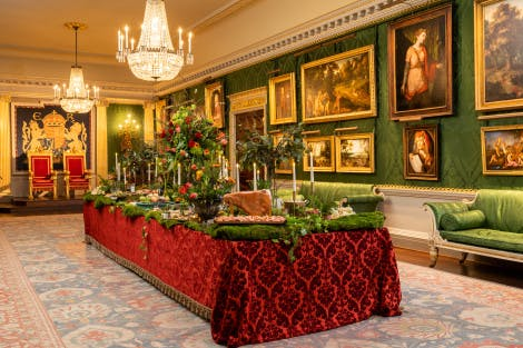 The Throne Room, lined with green silk damask and gold detailing is setup for a standing reception. A large central table is clothed in red damask and covered in fake moss, tealight candles and wooden food boards. A variety of food is displayed for self-service.