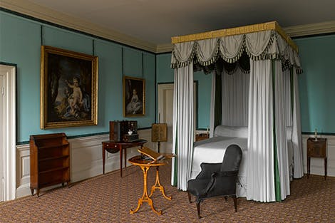 Queen Charlotte's bed decorated with white bed linen and the black horsehair chair in which she died at Kew Palace