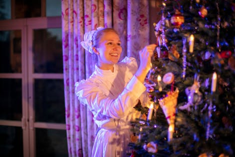 Explainer dressed as a Victorian, decorating a Christmas tree.