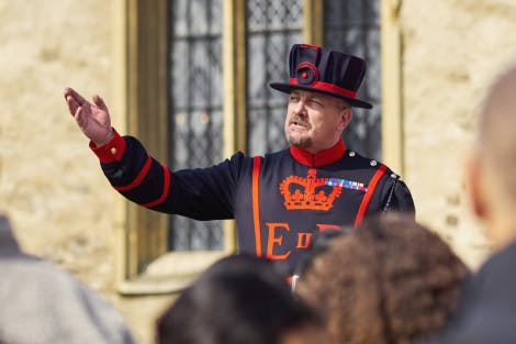 A Yeoman Warder gives a tour to a group of visitors outside the chapel of St Peter Ad Vincula at the Tower of London