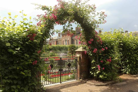 The gate of the Sunken Garden woven with plants and flowers at Kensington Palace under a partially cloudy sky