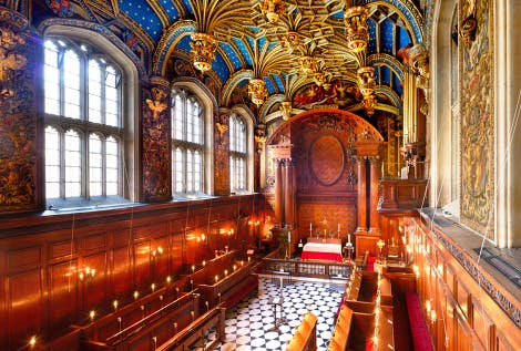 A high-level view of the Chapel Royal at Hampton Court Palace, looking down over the dark brown choir stalls and chequered floor, along the stone Tudor windows and blue painted vaulted ceiling.