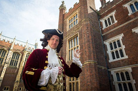 Georgian architect stands in Clock Court at Hampton Court Palace, looking up at the Tudor building