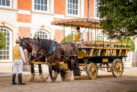 Two shire horses pull a tram, also known as a charabanc carriage, outside the baroque exterior of Hampton Court Palace
