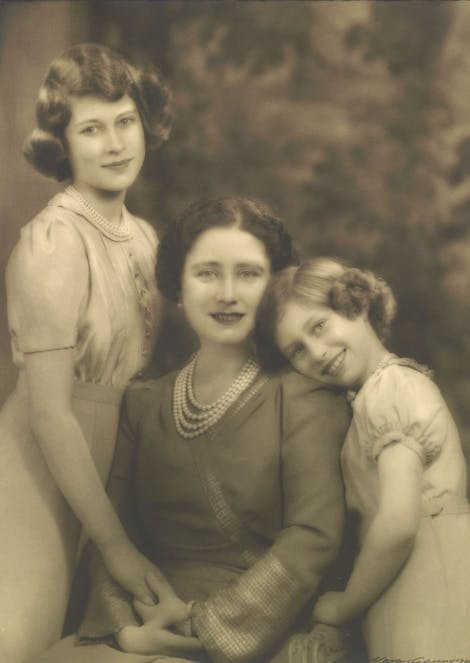 Sepia photograph of the Queen Mother when Queen, seated, with her daughters, Princess Elizabeth and Princess Margaret holding her hands on either side of their mother.