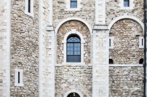 The White Tower detail, looking south. The focus of this image is on the first floor arches.   The White Tower was begun in the reign of William the Conqueror (1066-87) and completed by 1100. The fortress was originally faced with huge blocks of pale marble-like Caen stone imported from Normandy. In 1636-8 the external appearance of the White Tower was significantly altered with the replacement of much of its cut-stone work and window surrounds with Portland stone.   The primary role of the White Tower was as a fortress and stronghold but it also served as a royal residence and as the setting for major governmental and ceremonial functions.