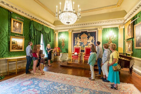 A guide shows a group of visitors the Throne Room in the State Rooms at Hillsborough Castle and Gardens. Two red and gold thrones sit at one end of the room and the walls are lined with green silk damask and the walls are lined with historical artwork.